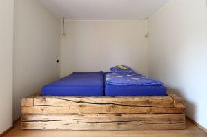 Holzbett aus Balken eines Abrisshauses